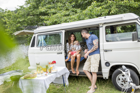 happy family with van at lakeside