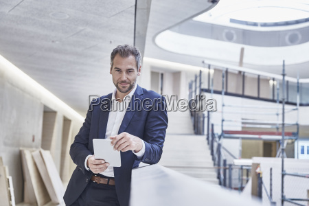 businessman holding tablet in office building