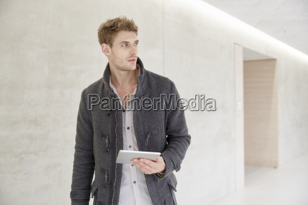 young man holding tablet looking around