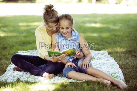 girl and young woman sitting on