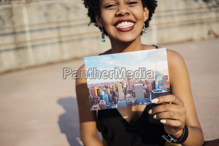 happy woman showing postcard of new