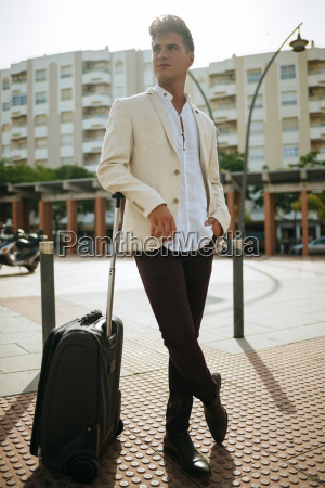 young man with suitcase looking around