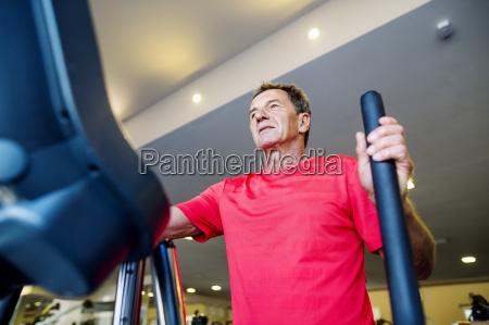 senior man exercising on step machine