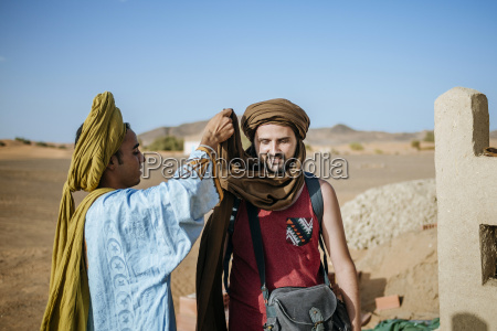 berber guide helping touist wrapping a