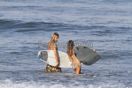 indonesia bali surfer couple going into