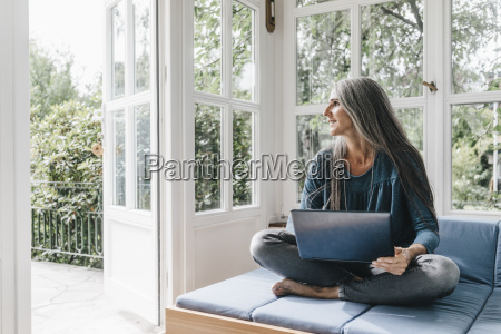 woman with laptop sitting on lounge