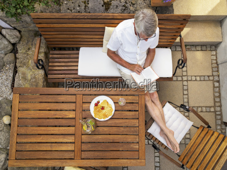 senior man sitting on terrace reading
