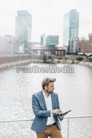 businessman standing on bridge using tablet