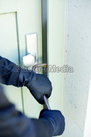 burglar with crowbar breaking door