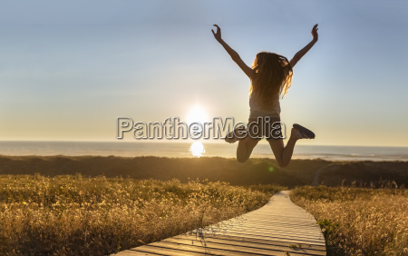 young woman jumping on boardwalk at