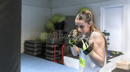 young woman in gym doing boxing