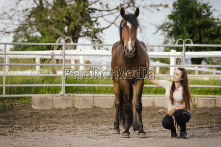 young woman with brown horse in