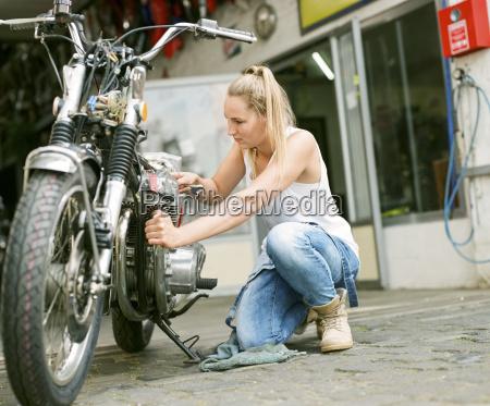 young woman repairing motorbike