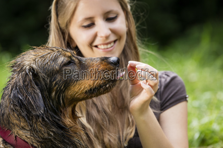 hand of woman feeding wet mongrel