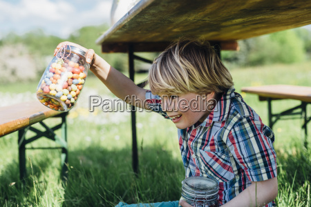 boy under beer table holding glass