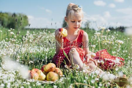 grl sitting in flower meadow with