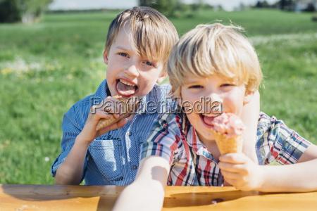 two boys eating ice cream cones