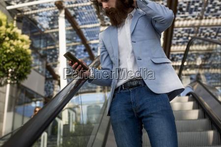stylish businessman using cell phone on