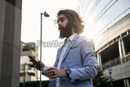 stylish businessman holding cell phone outdoors