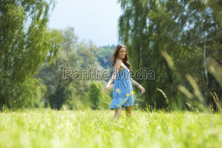 young woman blue dress on meadow