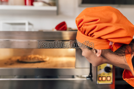 pizza baker looking into oven