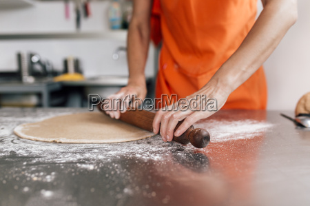 hands, of, woman, rolling, out, pizza - 19323553