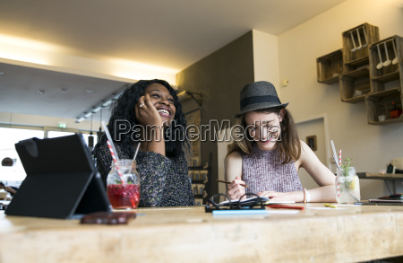 two friends using digital tablet in