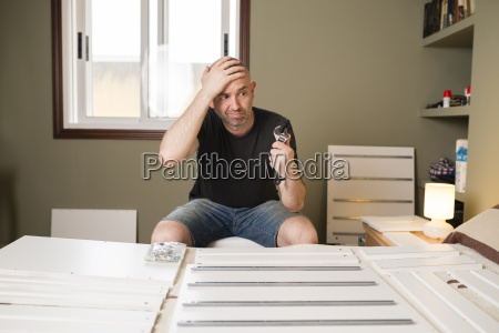 man assembling furniture at home looking