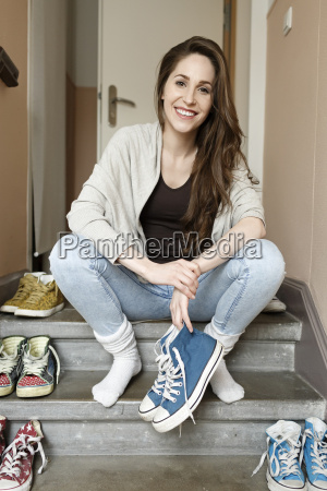 smiling young woman sitting on staircase