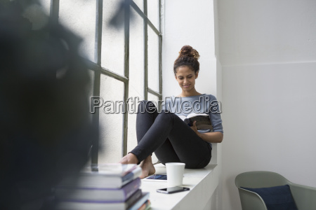 woman sitting on window sill reading