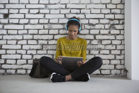 young woman with headphones sitting on