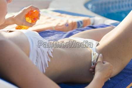 woman putting on sunscreen partial view