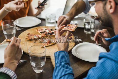 colleagues at table having a pizza