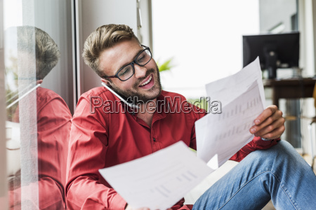 young man with documents talking on