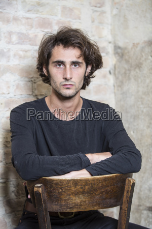 portrait of serious young man sittinmg