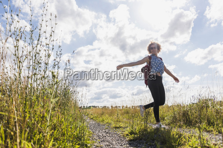 happy young woman on field path