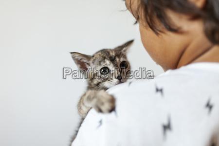 llttle boy holding kitten on his