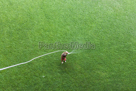 little boy standing on lawn playing