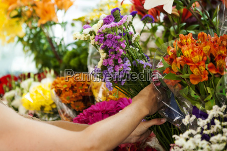 woman purchasing flowers on market partial