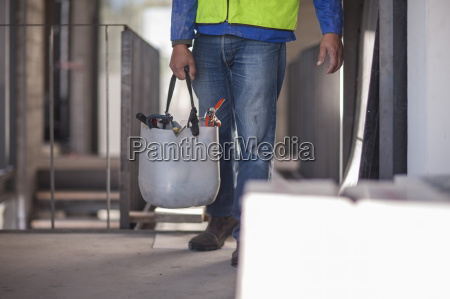 construction worker carrying bucket on construction