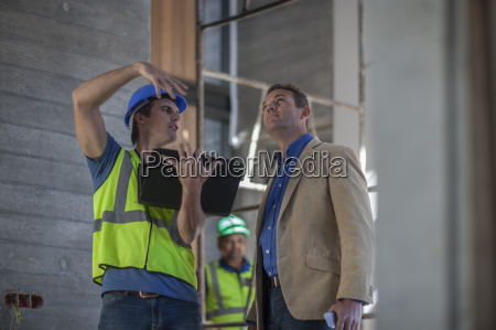 two men discussing on construction site