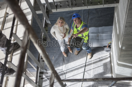 construction worker talking to woman on