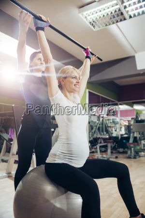 pregnant woman doing exercises in gym