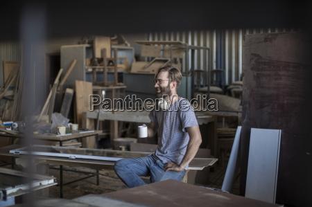 carpenter drinking coffee in workshop