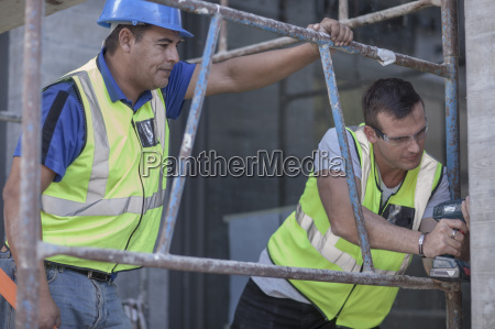 two construction workers on scaffolding working