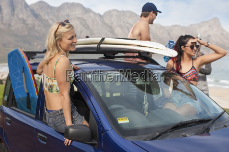 friends with surfboards on car at