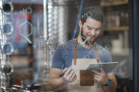 smiling man holding tablet with formula