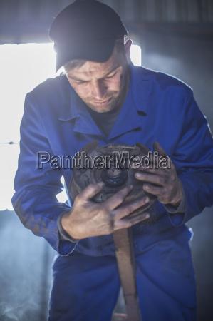 mechanic in workshop examining machine part