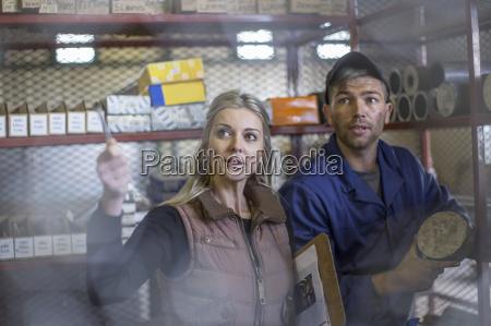 woman talking to worker in workshop