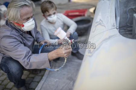 senior man spraying on car with